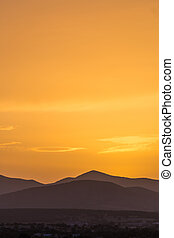 Scenic view of a beautiful rich orange sunset over the mountains