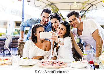 Group of young beautiful people sitting in a restaurant and taking a selfie