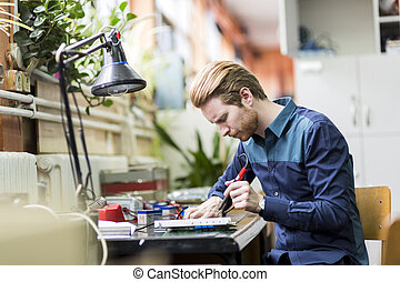 Young handsome man soldering a circuit board and working on...
