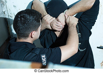 Putting handcuffs on a criminal - Brave police officer is...