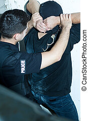Holding dangerous criminal - Strong police officer is...