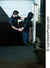 Police officer and criminal - Police officer is standing...
