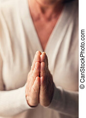 Woman praying - Hands of an unrecognizable woman in white...