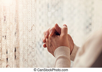 Woman praying - Hands of an unrecognizable woman standing by...