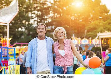 Senior couple at the fun fair - Senior couple having a good...