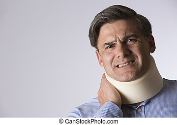 Studio Shot Of Man In Pain Wearing Neck Brace - Studio Shot...