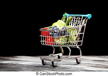 Shopping cart with vegetables on black background