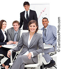 Assertive female executive sitting in front of her team in a...