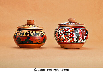 Two painted handmade ceramic pot with lids on kraft paper