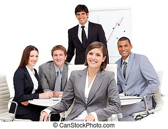 Charming businesswoman sitting in front of her team in a...