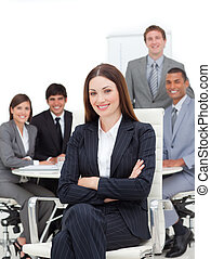 Smiling businesswoman sitting in front of her team in a...
