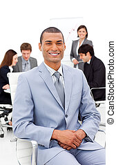 Charming businessman sitting in front of his team in a meeting