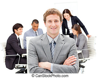 Assertive male executive with folded arms sitting in front...