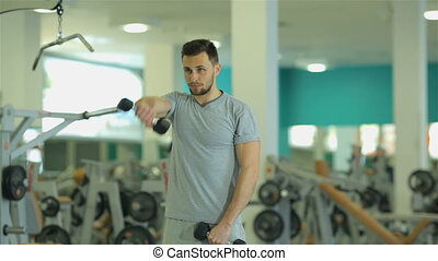 Young man doing exercise 2 with dumbbells for triceps