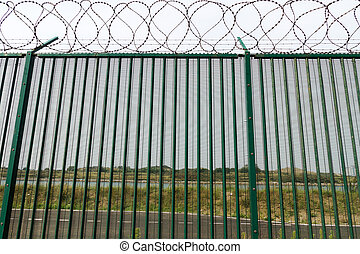 Green fence with razor wire guarding French ferry terminal -...