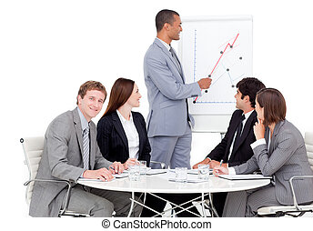 Self-assured businessman reporting sales figures to his team
