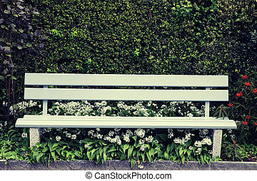 green wooden park bench at the summer garden