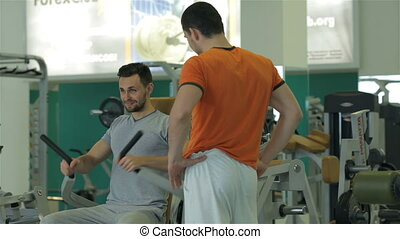 Man under his fitness trainer doing exercise for the chest muscles
