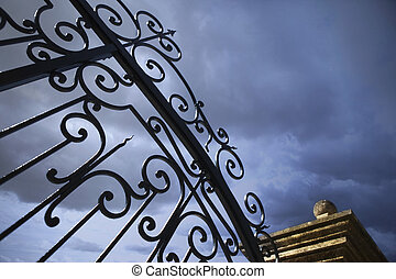 Wrought iron gate and stone pillar in a park