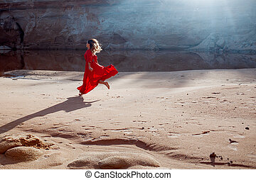 Woman in red waving dress with flying fabric runs on the...