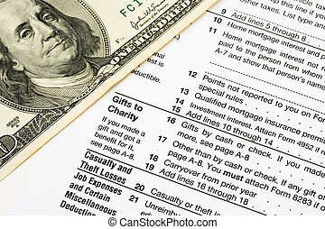 Tax Forms - One hundred dollar bills sitting on tax papers,...