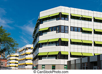 green and yellow sunblinds - white building with yellow and...