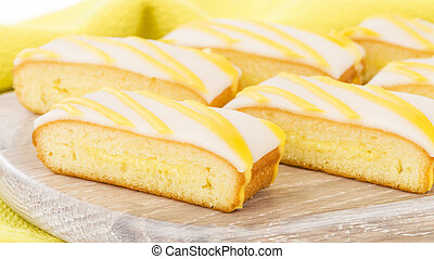 Lemon Drizzle Cake - Slices of lemon cake topped with icing....