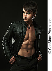 The muscular young sexy man on black background