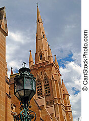 church steeple with lamp post and cloudy sky background