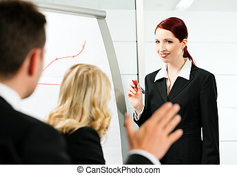 Business - presentation within a team; a female colleague is...