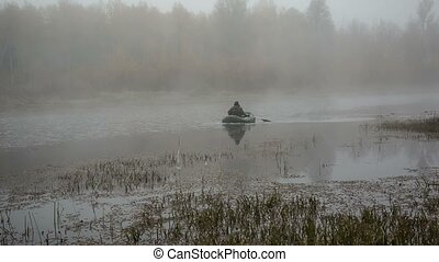 Man in a boat - a man in a boat floating on the lake in the...