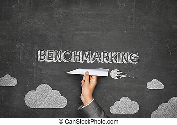 Benchmarking concept on blackboard with paper plane -...
