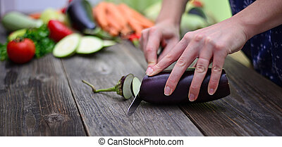 Woman's hand cut fresh eggplant