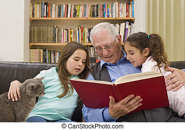 story time with grandpa - grandfather reading a story to his...