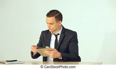 Young businessman puts the tablet takes the call and makes...