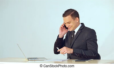 Smiling young businessman making a phone call and then enter...