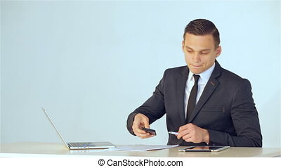 Young businessman puts a mobile phone