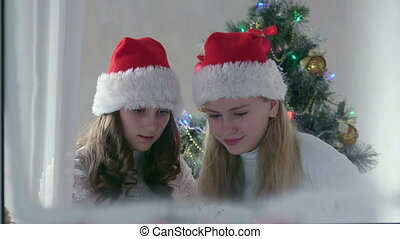 Little girls at home near Christmas tree