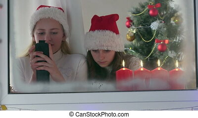 Little girls with gifted new smart phones at home near Christmas tree