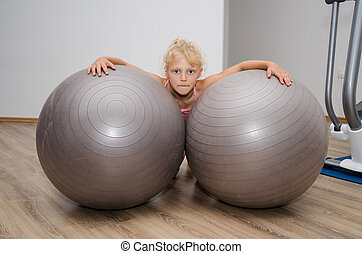 girl with two gym balls - little blond girl with two gray...