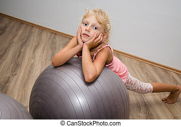 girl with gym ball - little blond girl lying over gray ball...