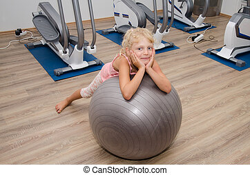 smiling girl in the gym - little blond girl lying over gray...