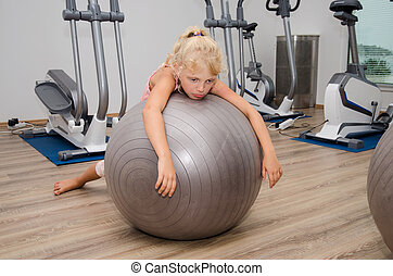 exhausted girl in the gym - tired little blond girl lying...