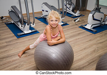 happy child in the gym - cute blond girl lying over gray...