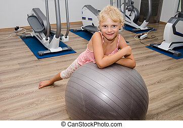 smiling girl and fit ball - cute blond girl lying over gray...