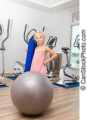 girl in gym - little blond girl in gym with sport equipment...