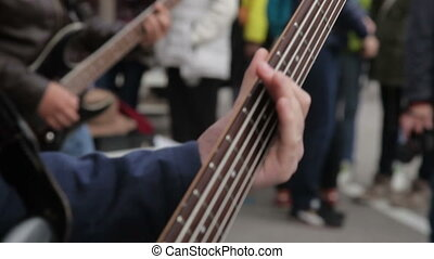 Young musician playing bass guitar in the street