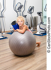 little girl with sport ball in gym - little blond girl in...