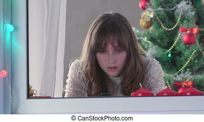 Girl using smart phone near Christmas tree something typing