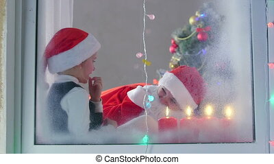 Mother in Santa Claus suit with his little daughter celebrate Christmas